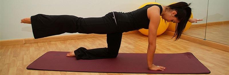 giovane donna realizzando esercizio Pilates